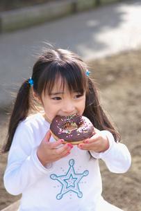 ドーナツを頬ばる女の子の写真素材 [FYI03244757]