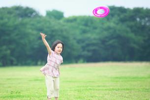 公園でフリスビーをする女の子の写真素材 [FYI03244758]