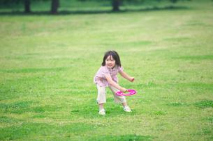 公園でフリスビーをする女の子の写真素材 [FYI03244791]