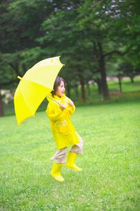 雨具で外を走る女の子の写真素材 [FYI03244794]