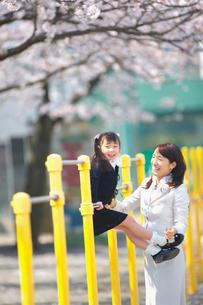 鉄棒をする女の子と母親の写真素材 [FYI03244854]