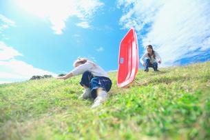 土手滑りをして遊ぶ親子の写真素材 [FYI03244958]