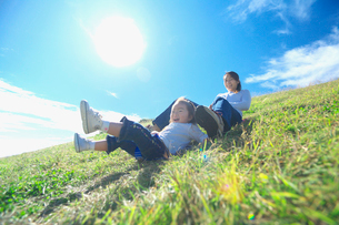 土手滑りをして遊ぶ親子の写真素材 [FYI03244959]