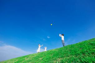 土手でボール投げをして遊ぶ親子の写真素材 [FYI03244971]