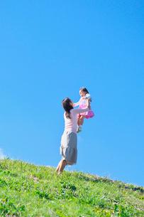 土手で子供を抱き上げる母親の写真素材 [FYI03244973]