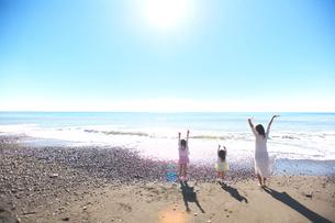 湘南海岸で万歳をする親子の写真素材 [FYI03244978]