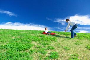 土手滑りをして遊ぶ親子の写真素材 [FYI03244981]