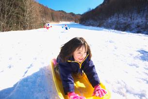 ソリで雪滑りをする女の子の写真素材 [FYI03245071]