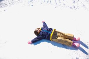 雪原に仰向けに寝た女の子の写真素材 [FYI03245073]