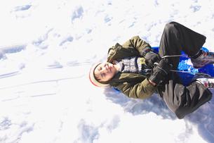 ソリで雪滑りをする男の子の写真素材 [FYI03245074]