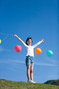 風船を持って両手を広げる少女の写真素材 [FYI03245390]