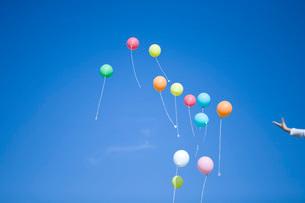空を舞う風船と少女の手の写真素材 [FYI03245393]