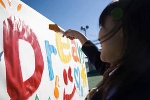 野外のボードに絵を描く女子学生の写真素材 [FYI03245974]