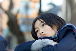 鉄棒にもたれるマフラーをした女子学生の写真素材 [FYI03246099]