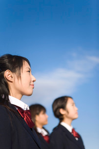 前を見上げる女子学生と青い空の写真素材 [FYI03246101]