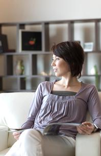 ソファーで雑誌を広げる女性の写真素材 [FYI03246142]