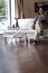 ソファーで寛ぐ男性と犬の写真素材 [FYI03246155]