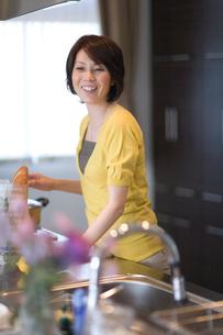 笑顔でキッチンに立つ女性の写真素材 [FYI03246159]