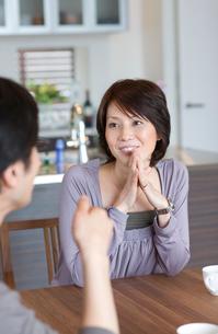 ダイニングテーブルで会話する男女の写真素材 [FYI03246162]
