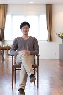 ダイニングで椅子に座る男性の写真素材 [FYI03246171]