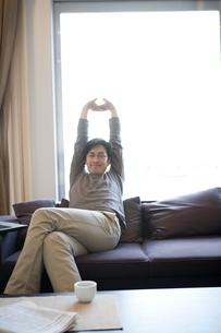 ソファーで伸びをする男性の写真素材 [FYI03246172]