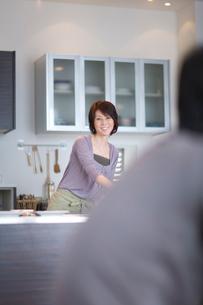 キッチンに立つ女性とダイニングにいる男性の写真素材 [FYI03246179]