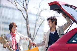 赤い車に荷物をつむ男女の写真素材 [FYI03246183]