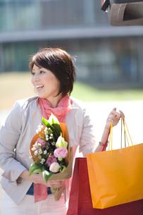 買い物袋と花束を持つ女性の写真素材 [FYI03246205]
