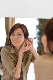 鏡の前でアクセサリーをつける女性の写真素材 [FYI03246221]