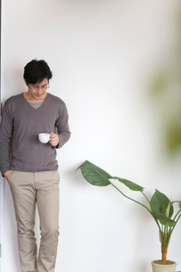 コーヒーカップを片手に壁際に立つ男性の写真素材 [FYI03246225]