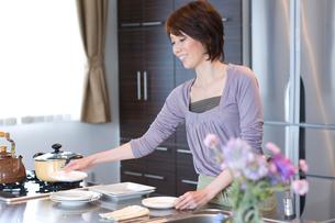 皿を持ってキッチンに立つ女性の写真素材 [FYI03246230]