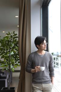 コーヒーカップを片手に窓辺に立つ男性の写真素材 [FYI03246243]