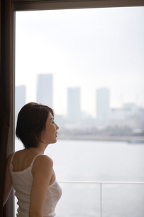 窓辺に立ち外を見る女性の写真素材 [FYI03246247]