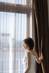 窓辺に立ち外を見る女性の写真素材 [FYI03246250]
