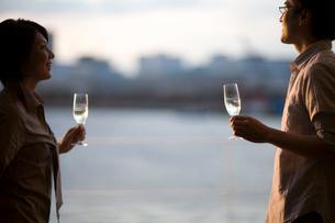 窓辺でワイングラスを手に会話する男女の写真素材 [FYI03246253]