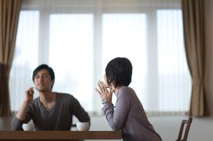 ダイニングテーブルで会話する男女の写真素材 [FYI03246257]