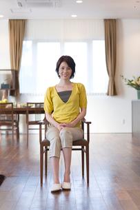 ダイニングで椅子に座る女性の写真素材 [FYI03246263]