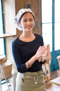 布巾を持つカフェで働く女の子の写真素材 [FYI03246291]