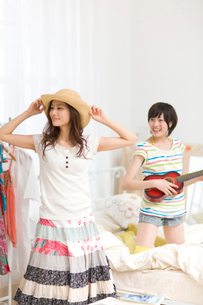 帽子を被る女の子とミニギターを持つ女の子の写真素材 [FYI03246306]
