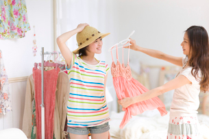 部屋で洋服を合わせる2人の女の子の写真素材 [FYI03246349]