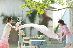 テーブルクロスを広げる2人の女の子の写真素材 [FYI03246353]
