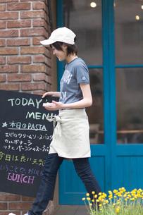 メニューボードを運ぶ女の子の写真素材 [FYI03246361]