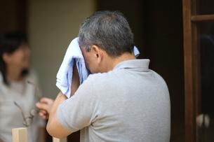 庭先で汗をタオルで拭う父親の写真素材 [FYI03246440]