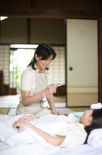 布団に横になる娘を看病する母親の写真素材 [FYI03246460]