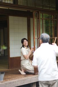 縁側と庭先を掃除する夫婦の写真素材 [FYI03246481]