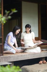 縁側でアルバムを見る母親と娘の写真素材 [FYI03246510]
