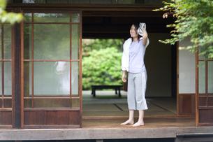 縁側でタオルで頭を拭く女の子の写真素材 [FYI03246512]