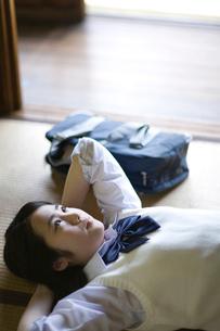 座敷に仰向けで考え事をする女の子の写真素材 [FYI03246517]