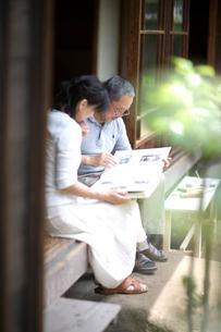 縁側でアルバムを見る夫婦の写真素材 [FYI03246518]