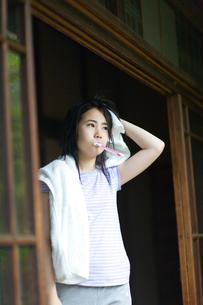 縁側で歯を磨きながら頭を拭く女の子の写真素材 [FYI03246540]